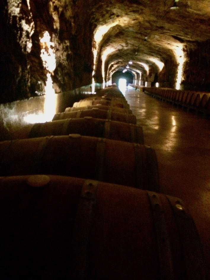 Tønner på tønner med vin ligger lagret i gangene.